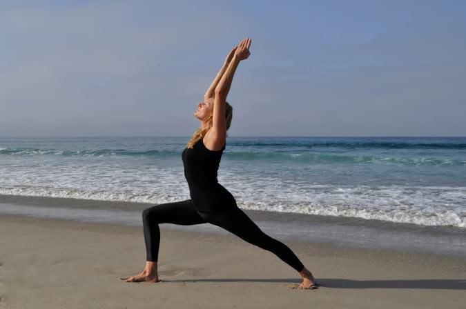 posizione yoga del guerriero sulla sabbia