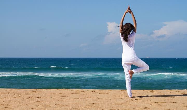 ragazza che fa yoga al mare